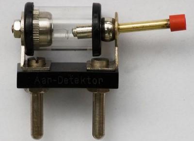 Detektor, fungující jako hrotová dioda, sestával ze skleněného pouzdérka, ve kterém byl uchycen galenitový krystal, do kterého se píchalo pružnou jehličkou aretovanou v kloubovém držáčku tak dlouho, až byl příjem optimální a dostatečně hlasitý. Poté bylo možné ještě drobné doladění otočným kondenzátorem, což bylo potřeba hlavně v případech, kdy naladěný program rušila další blízká silnější stanice. Pochopitelně bylo nutno krystalku, mimo připojení ke kvalitní drátové anténě, také dobře uzemnit. Jinak jste se poslechu rádia nedočkali. Nastavování detektoru vyžadovalo neskutečnou trpělivost, často stačilo pak o naladěný přijímač neopatrně zavadit rukou a celá legrace s pícháním do krystalu se opakovala nanovo. Detektor je na snímku zobrazen zhruba ve skutečné velikosti, dokonce se dal /za pár korun/ ještě okolo roku 1961-2 koupit v prodejnách s elektropotřebami. Vím to dobře, krystalku jsem stavěl jako mladý hoch také…
