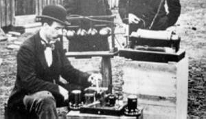 První pionýrské pokusy Gugliema Marconiho. Zařízení před G. Marconim je zřejmě vysokofrekvenční transformátor, na podstavcích je vidět mohutné kulové jiskřiště /vlevo/ a válcový koether, který sloužil jako přijímač. Všimněte si absence jakýchkoliv elektronek. Ty byly vynalezeny o několik let později...