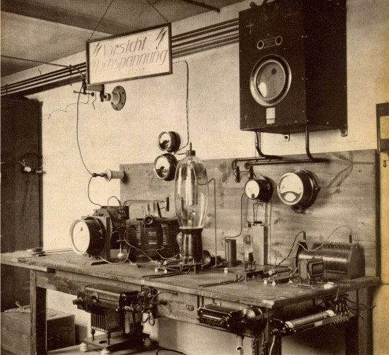 """Vysílací pracoviště v Německu v roce 1923. Trochu to připomíná, zvláště skalnímu radioamatérovi, jeho domácí """"bastlířský"""" koutek. Ale opak je pravdou, jedná se o profesionální zařízení té doby. Zařízení na stole jsou pečlivě rozmístěna a natrvalo zafixována do jeho desky. Dole, na spodním patře stolu, vidíme VN transformátor s usměrňovačem, soudě podle vzhledu, selenovým. O tom, že se zde napětí pohybuje hodně nad tisícem voltů, svědčí jeho umístění na porcelánových izolačních podložkách. Na obvodu stolové desky najdeme pak regulátory žhavení a katodového předpětí, provedené jako válcové reostaty a sadu spínačů. Hlavními aktéry dění jsou však dvě elektronky; ta menší je evidentně budič a velká trioda vejčitého tvaru je vlastní vysílací elektronka. Od ní pak pokračuje signál přes laditelný RC článek opatřený měřením VF anténního proudu silným vodičem umístěným co nejdále od všech předmětů a zdi /nutné po správnou impedanci svodu/ven k anténě. Nahoře, částečně zakryté varovnou cedulí """"Vorsicht Hochspannung!"""" /Pozor vysoké napětí/ je uzemněné jiskřiště s malými kulovými elektrodami, jako ochrana před atmosférickou elektřinou a přímým úderem blesku. Tmavá skříň s měřidlem zavěšená na zdi, je patřičně dimenzovaný zdroj stejnosměrného napětí pro katodu přímožhavené vysílací triody, o čemž vypovídá ostatně i síla vodičů, které z ní vycházejí. Velikost vysílací triody a zobrazená podpůrná zařízení odpovídají nominálnímu výkonu vysílače nejvíce tak 1 - 2 kW."""