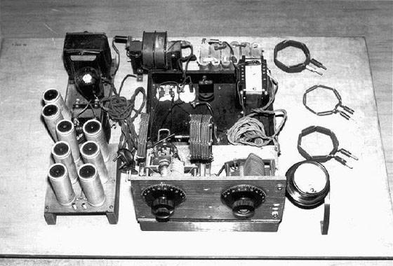 Formisův vysílač. Vlevo vidíme oddělený napájecí zdroj s vakuovou usměrňovací diodou, transformátorem a sadou filtračních kondenzátorů. Zajímavé je ladění dvěma nespřaženými otočnými kondenzátory. Nahoře je nad vysílačem zřejmě žhavící transformátor pro vysílací elektronku, sada šesti baterií pro žhavení modulátoru /domnívám se/ * sada výměnných cívek pro různá pásma a kulatý měřící přístroj. Ten sloužil buď ke kontrole modulace, ale zřejmě k přímému měření vf anténního proudu, jak bylo tehdy zvykem. Snímek zapůjčilo NTM v Praze.  * Formis používal, zřejmě pro co nejvyšší možnou čistotu modulace a zamezení síťového brumu, bateriové žhavení modulátoru. Vysílač na snímku ale není zřejmě kompletní; chybí koncový stupeň a některé elektronky, včetně vysílací. Není tedy známo, zda Formis použil jednoduchý koncový stupeň s jednou elektronkou, či dvojčinné zapojení se dvěma elektronkami v páru.