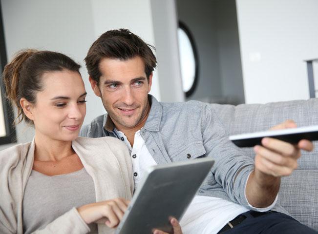 Muž přepíná programy na hlavní televizi v domácnosti. Žena sleduje své pořady na tabletu. Ilustrační foto Shutterstock.com