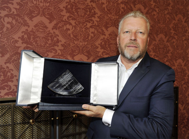Ředitel soutěže Jiří Besser předvádí moderní křišťálovou trofej sgrafikou jedné z Janáčkových partitur pro ceny CLASSIC PRAGUE AWARDS. Zdroj foto: classicpragueawards.eu