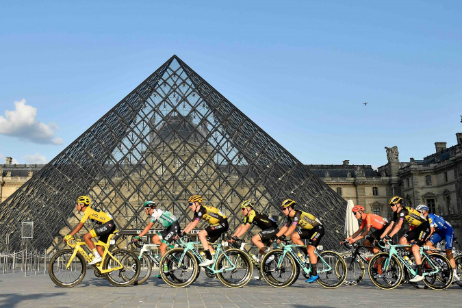 TOPSHOT - Colombia's Egan Bernal (L) of Team Ineos wears the overall leader's yellow jersey as he passes with the pack past the pyramid of The Louvre Museum designed by Ieoh Ming Pei during the twenty-first and final stage of the 106th edition of the Tour de France cycling race between Rambouillet and Paris Champs-Elysses in Paris on July 28, 2019. (Photo by Julien DE ROSA / POOL / AFP) / RESTRICTED TO EDITORIAL USE - MANDATORY MENTION OF THE ARTIST UPON PUBLICATION - TO ILLUSTRATE THE EVENT AS SPECIFIED IN THE CAPTION        (Photo credit should read JULIEN DE ROSA/AFP via Getty Images)